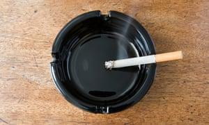 Burning cigarette in a black ashtray