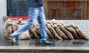 A man walks past sandbags