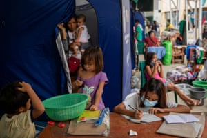 Daniella Nicole Cabasines, 11, a grade 5 student, carries on her learning at an evacuation centre for residents affected by Typhoon Vamco. 'When the flood started to rise, the first thing on my mind was to save my modules. I forgot about my clothes, but not my modules,' she said.