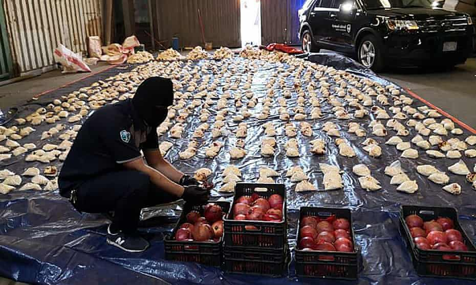 A Saudi customs officer opens imported pomegranates containing Captagon pills in Jeddah.