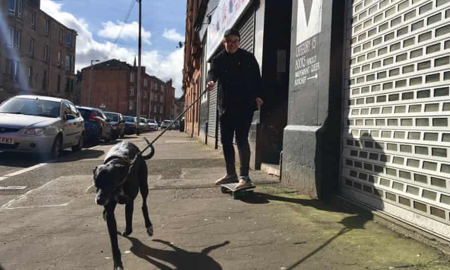 Charlotte from Category Is Bookshop in Glasgow out delivering by skateboard with her dog.
