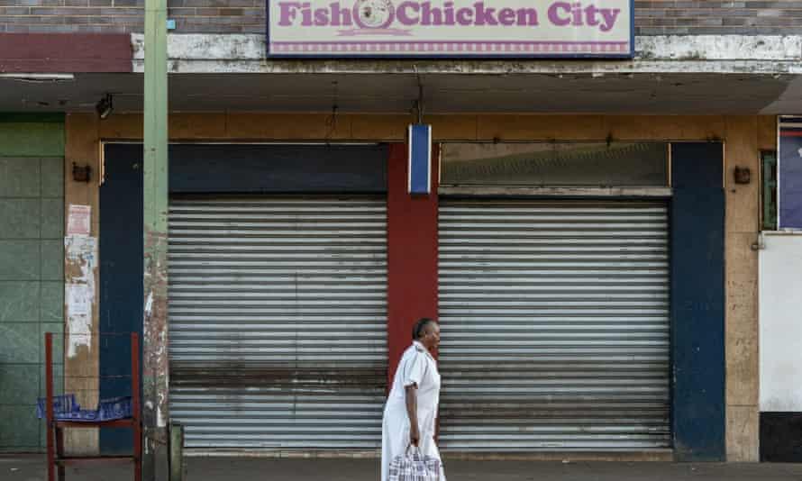 A health worker walks past closed shops in Bulawayo, Zimbabwe.