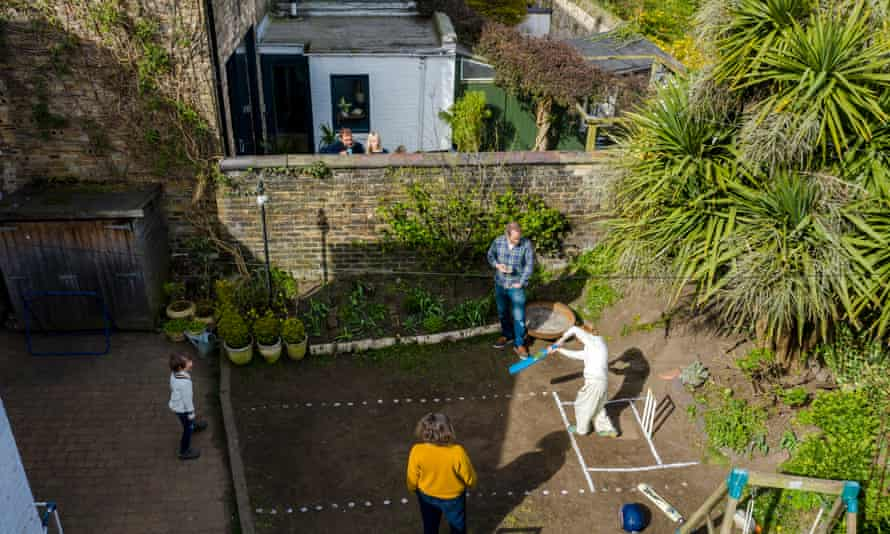Peter and Sarah playing cricket in their garden with sons Oscar and Felix, with Chad and Clare Hudson looking over the wall
