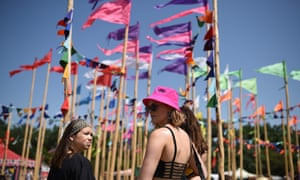 Revellers walk past flags during the Glastonbury Festival of Music and Performing Arts on Worthy Farm near the village of Pilton in Somerset.