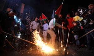 Palestinian hold flames and signs reading 'We will return' during a rally in the West Bank city of Hebron