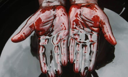 A man covers his hands in crude oil during a protest against oil spills in Bonga, Nigeria.