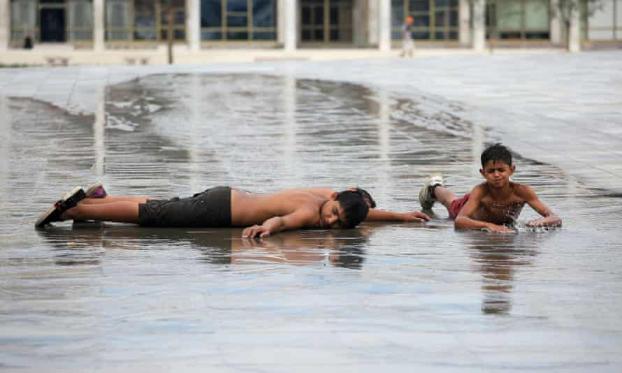 Children cool off in water on a square in Tirana, Albania.