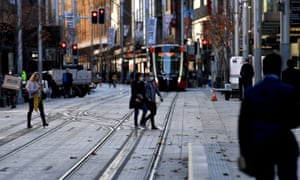 People wearing face masks cross a street in the Sydney CBD as the NSW government locked down several central areas of the city