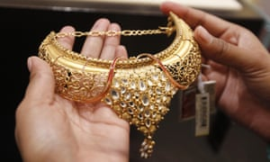 A woman shops for a gold necklace at a jewellery showroom. ahead of the Diwali festival. One Indian tycoon has give employees gifts of jewellery and cars to celebrate the annual festival.
