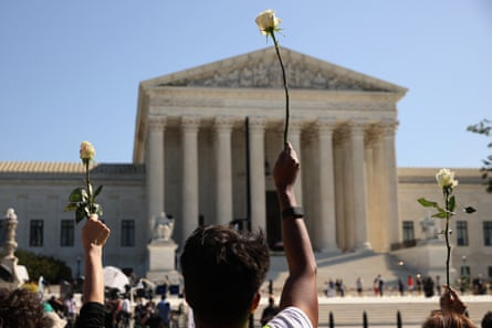 Members of Casa, an advocacy organization for Latino and immigrant people, hold up white roses in honor of Ruth Bader Ginsburg at the supreme court on Wednesday.