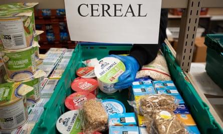 A volunteer picks food for a food parcel