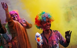People dance as others throw coloured powder during Holi celebrations in New Delhi.