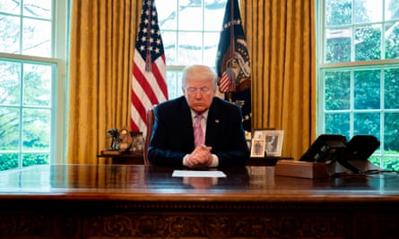 Donald Trump prays at his desk in the Oval Office, as he participates in an Easter Blessing.