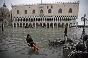 A woman sits in a chair in a flooded St Mark's Square, Venice.