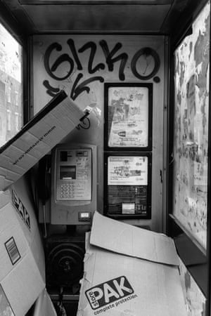 A phone box in Commercial Road, Tower Hamlets, filled with cardboard boxes