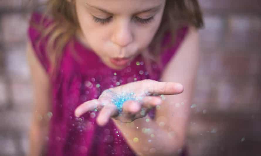 Girl blowing plastic glitter