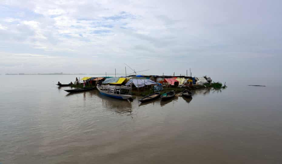 Villagers take shelter on an island they have made out of boats and rafts in the flood waters of Morigaon district of Assam state