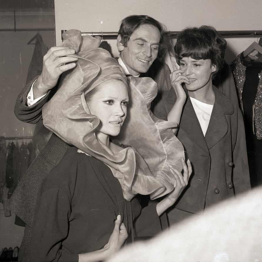French couturier Pierre Cardin, and a model show an extravagant hat to his friend, actress Jeanne Moreau, right, in 1963.
