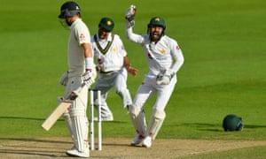 Pakistan's Mohammad Rizwan celebrates taking a catch to dismiss England's Joe Root.
