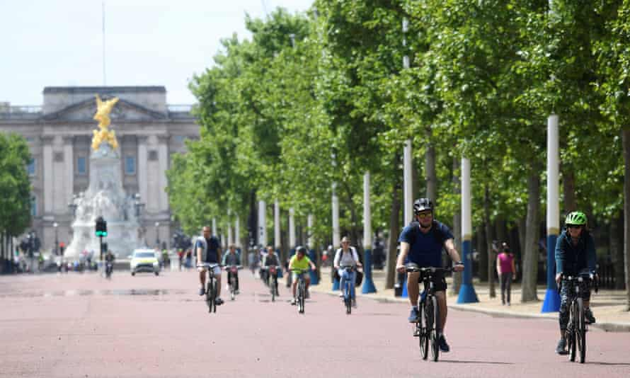 People are seen cycling along the Mall, London, on 17 May.