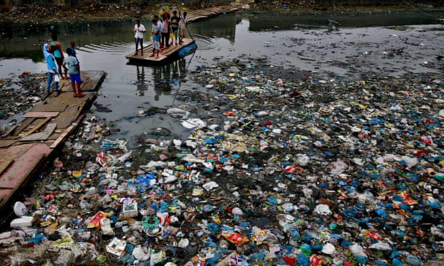 A man punts a raft across a canal in Mumbai, India, that is clogged with plastic waste