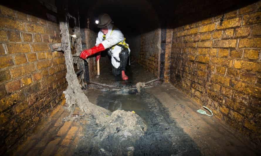 A member of Thames Water's sewer team points out wet wipes clogging up the sewer in Putney, London