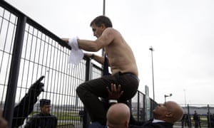 Air France human resources chief Xavier Broseta is helped across a fence by security and police officers