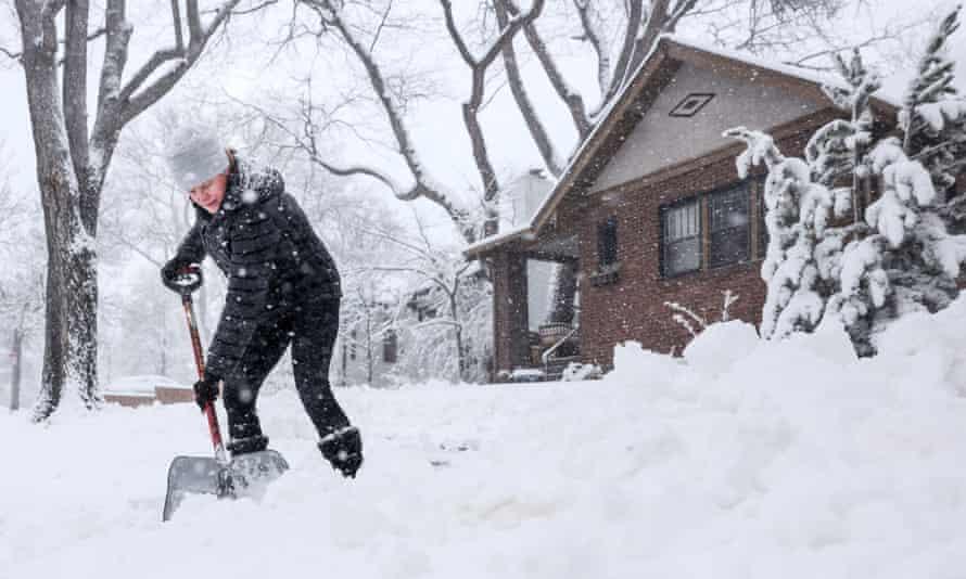 Kathy Gomez shovels her sidewalk in Denver, Colorado.