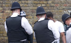 Police search black youths at the entrance to Notting Hill Carnival