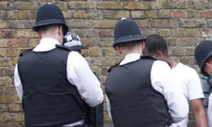 Police question and search young men in London.