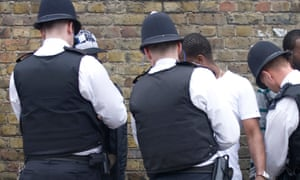 Police search a group of young men in London.