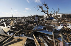 A man walks over what remains of homes in the area called the Mudd after it was devastated by Hurricane Dorian.