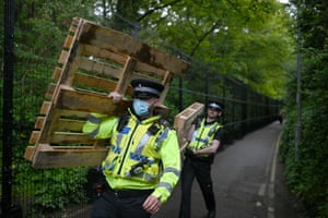 Officers carry pallets outside the security fence erected around the perimeter of Tregenna Castle near St Ives