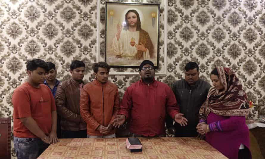 A pastor is conducting a special prayer for a Christian family in Aligarh. Indian Christians make up approximately 2.3% of the country's population.