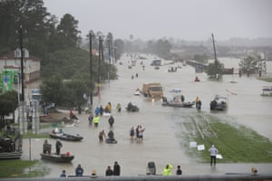 People walk down a flooded street as they evacuate their homes in Houston, Texas Monday.