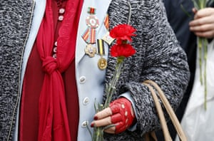 A liquidator of the consequences of the Chernobyl's disaster holds flowers during a ceremony to commemorate the victims