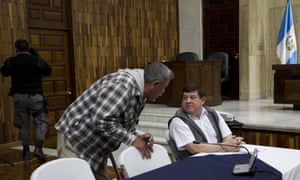 Former army officer Esteelmer Francisco Reyes Girón, sitting, talks with former paramilitary fighter Heriberto Valdez Asij during their trial for sex abuse in Guatemala City.
