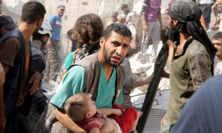 A Syrian man carries an injured child at the site of air attacks by Assad's forces on a residential area in Aleppo.