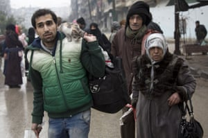 Syrians leave a rebel-held area of Aleppo towards the government-held side