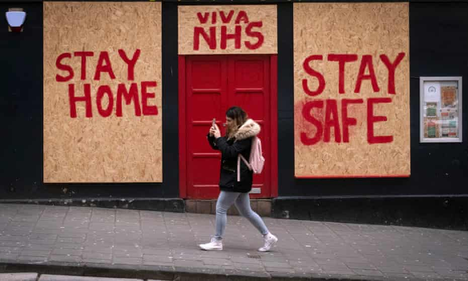 A woman walks past a boarded up restaurant in Edinburgh as the UK's lockdown is set to be extended.