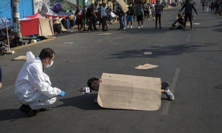 A television journalist interviews an 18-year-old as he blocks an avenue in a protest against authorities for not being helped to return to his home province, in Lima, Peru, on 30 April.