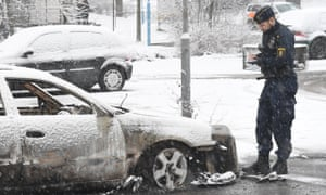 A policeman investigates a burnt-out car in Rinkeby after the riot last week.