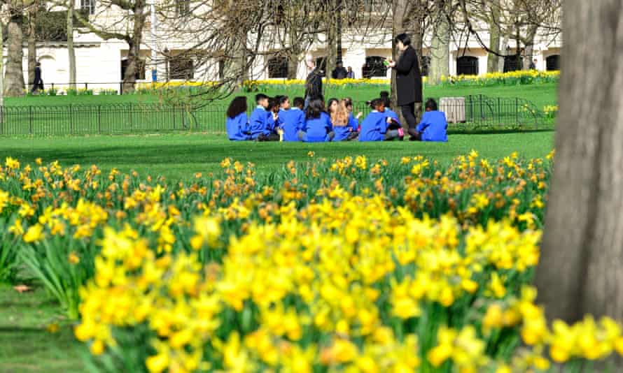 A group of primary school children have a picnic in St James's Park, London. Overseas school trips have been stopped due to coronavirus concerns, but schools remain open for the time being.