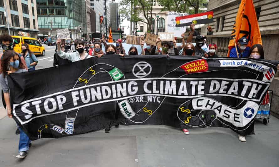 activists hold sign that says 'stop funding climate death'