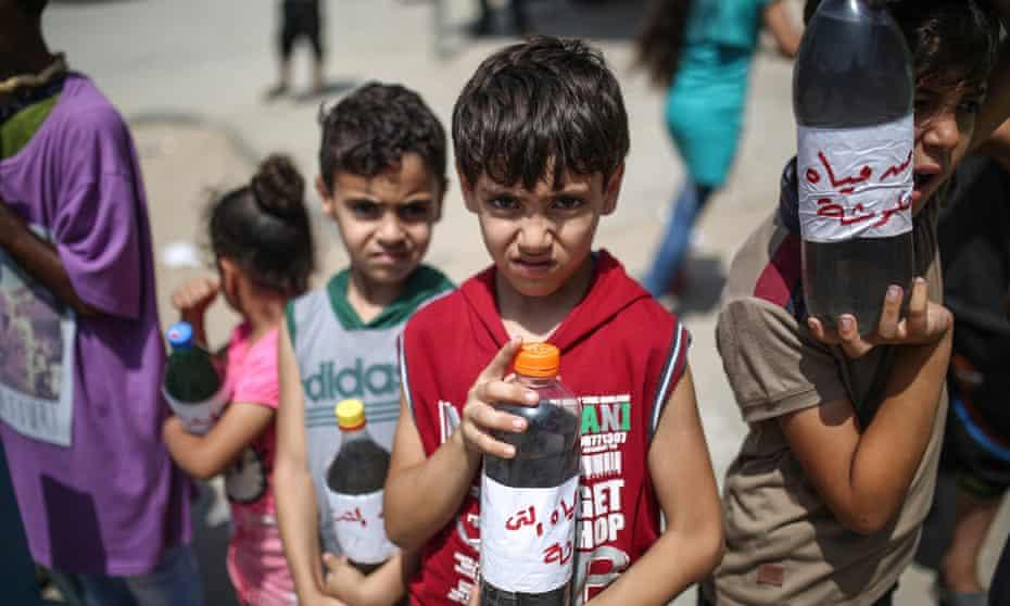 Children at a protest demanding clean water stand before Beit Hanoun border gate in Gaza City