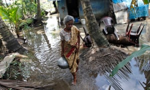A Sri Lankan flood victim carries a pot of drinking water at her submerged compound in Kartivu.