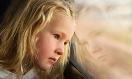 Sad child looking out of car window