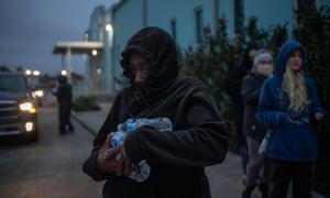 A woman carries bottled water she received from a warming center and shelter in Galveston.
