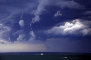 Boats head to shore as storm clouds move along the coast