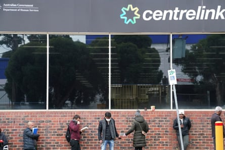 People queue outside a Centrelink office in Melbourne on 24 March.